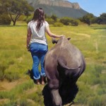 portrait of a young woman in landscape with rhino